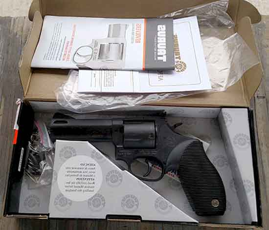 Taurus Tracker .44 Magnum In The Box, with a lock, one extra grip, and manual