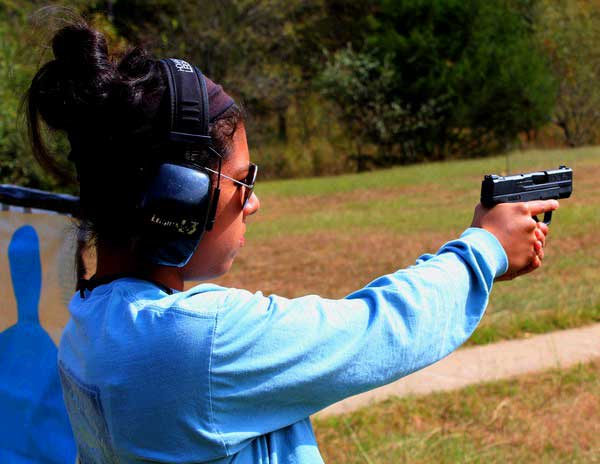 The 9mm S&W Shield in the shooting grip of a 5' 2